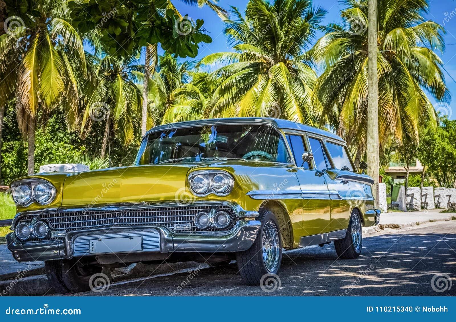 HDR - Американский золотой Форд Brookwood припаркованное под ладонями около пляжа в Варадеро Кубе - репортаже Serie Кубы