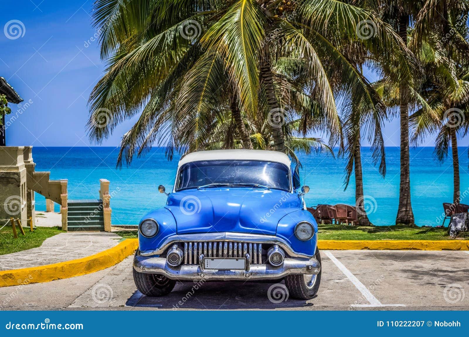 HDR - Amerykański błękitny klasyczny samochód parkujący pod palmami na plaży w Varadero Kuba, Seria Kuba reportażu -