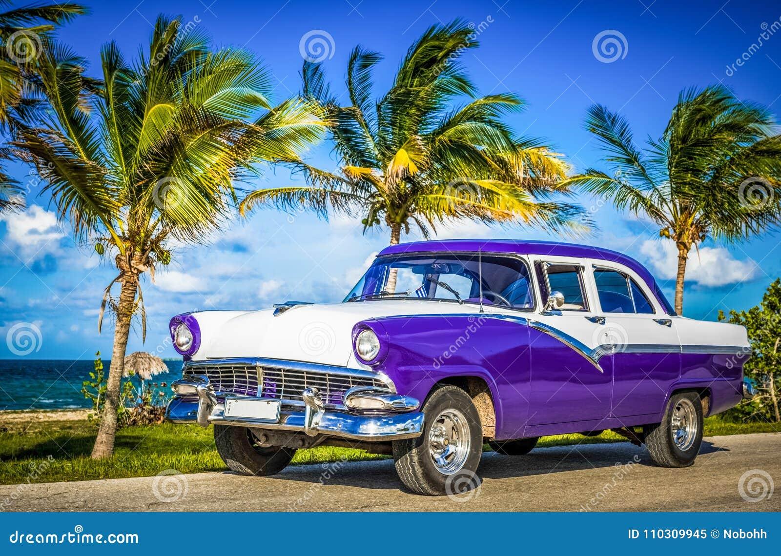 HDR - Coche azul blanco americano parqueado del vintage en la opinión del delantero-lado sobre la playa en Havana Cuba - el repor