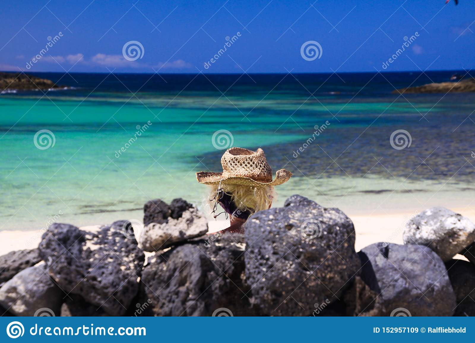 Head of blonde woman with straw hat sitting behind wall of piled natural rocks on beach with turquoise ocean - Fuerteventura, El