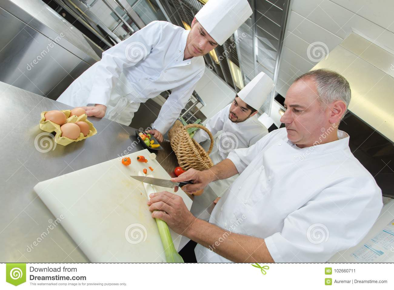 Head-chef teaching colleagues how to slice vegetables
