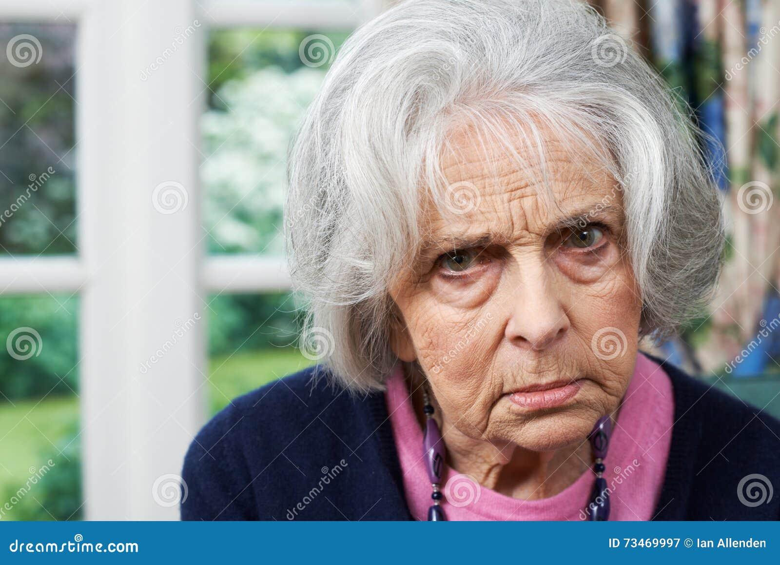 Head och skuldrastående av den ilskna höga kvinnan hemma