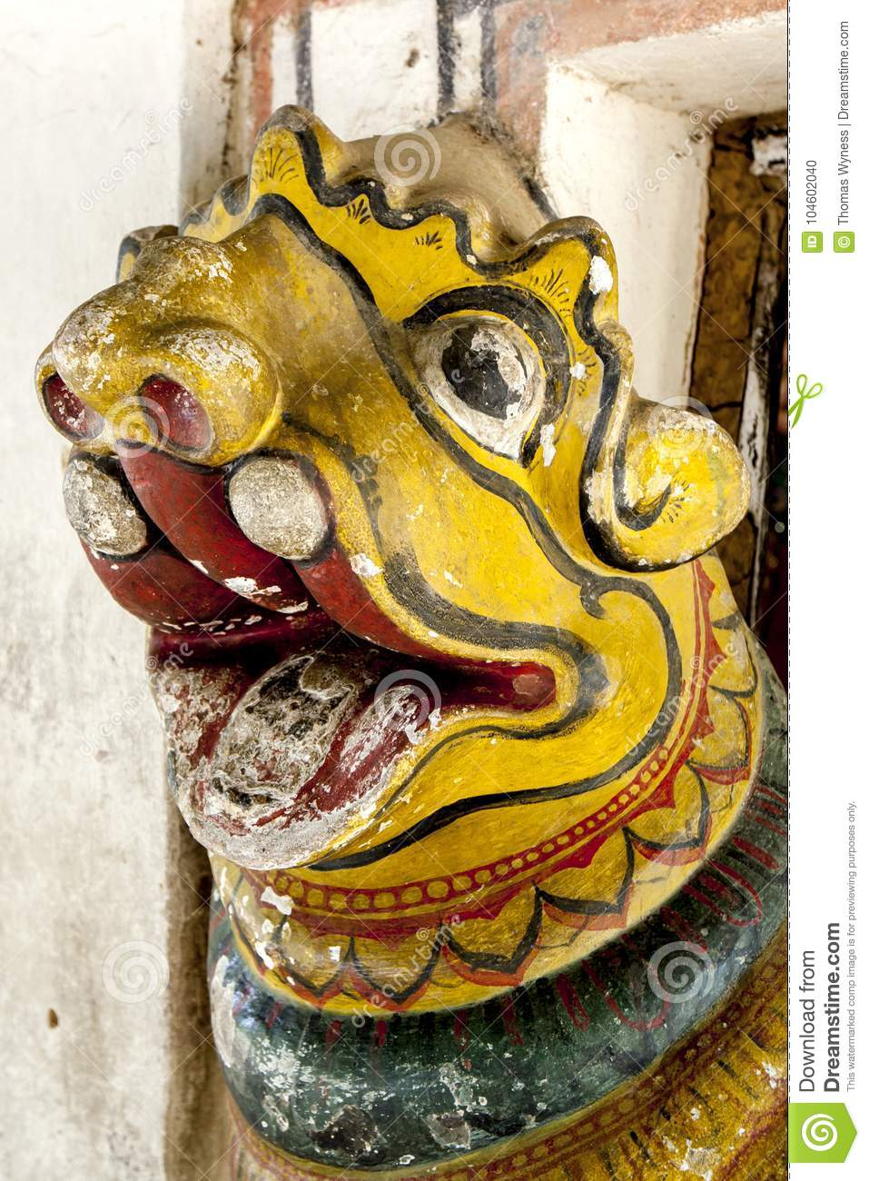 The head of one of the ancient lion statues which guards the entrance door to the main shrine at Embekke Devale.