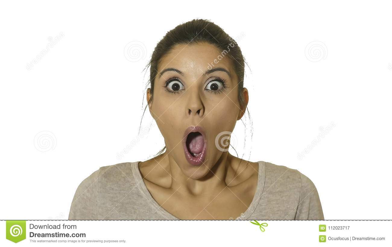 Head portrait of young happy and excited hispanic woman 30s in surprise and astonished face expression eyes and mouth wide open is