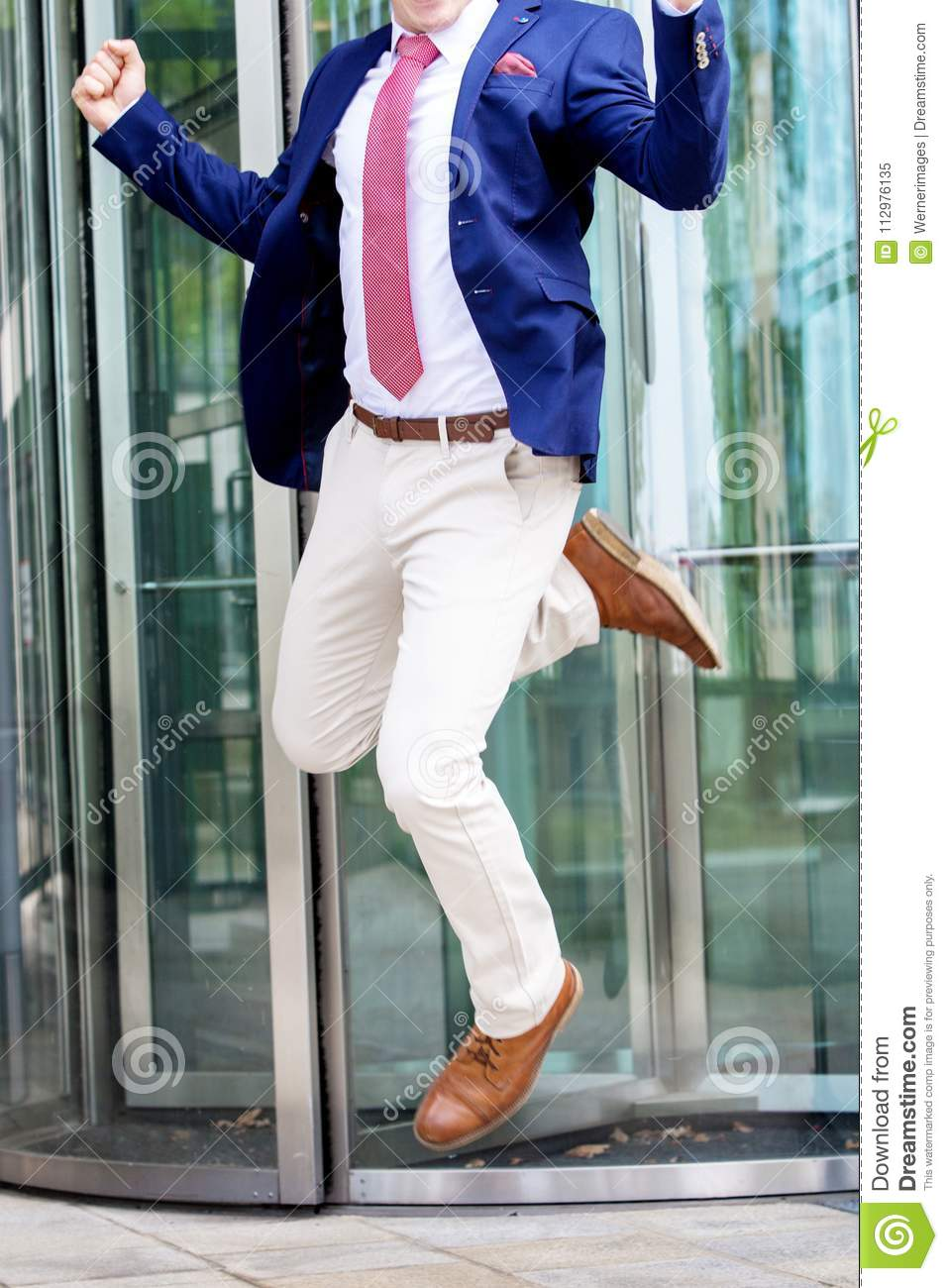 Headless businessman jumping in front of office building