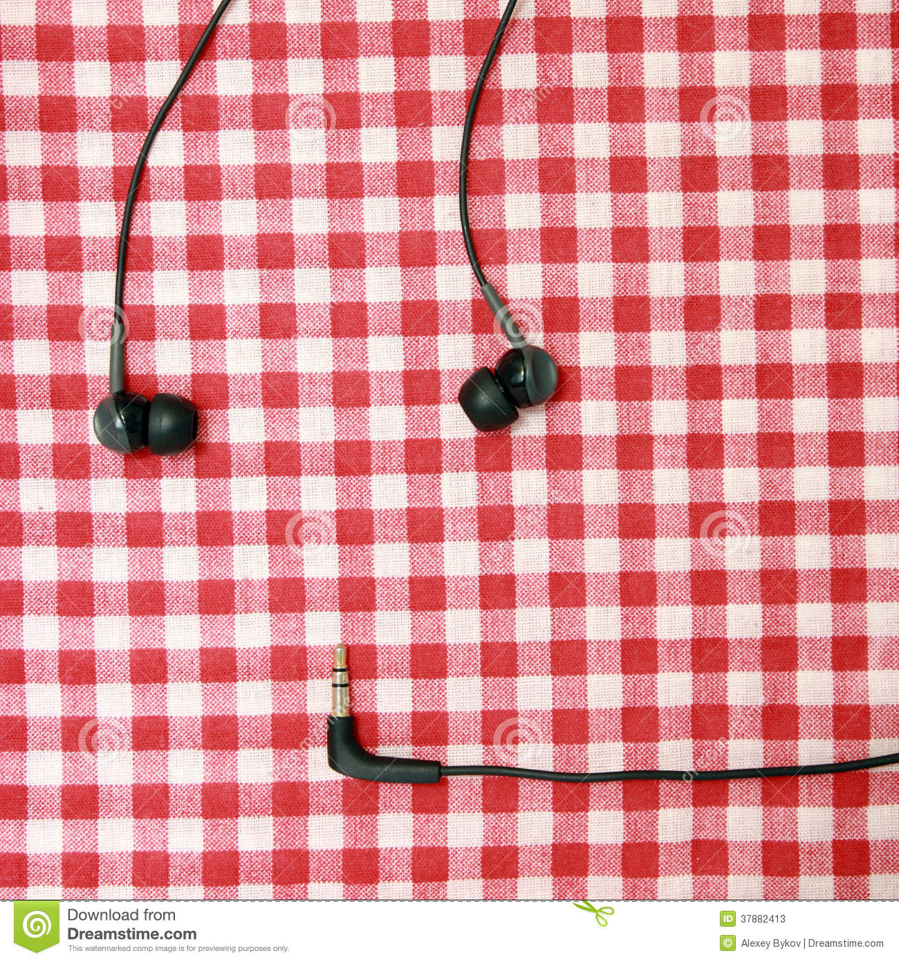 Headphones on a red bed sheet.