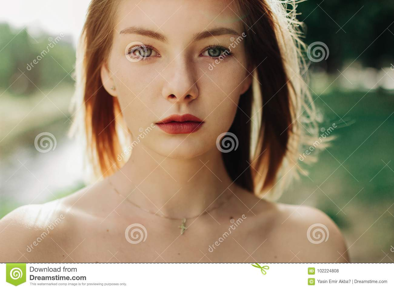 4ada4f87f2b Young beautiful Bosnian girl looking at camera in a sunny day next to river in  nature in summer