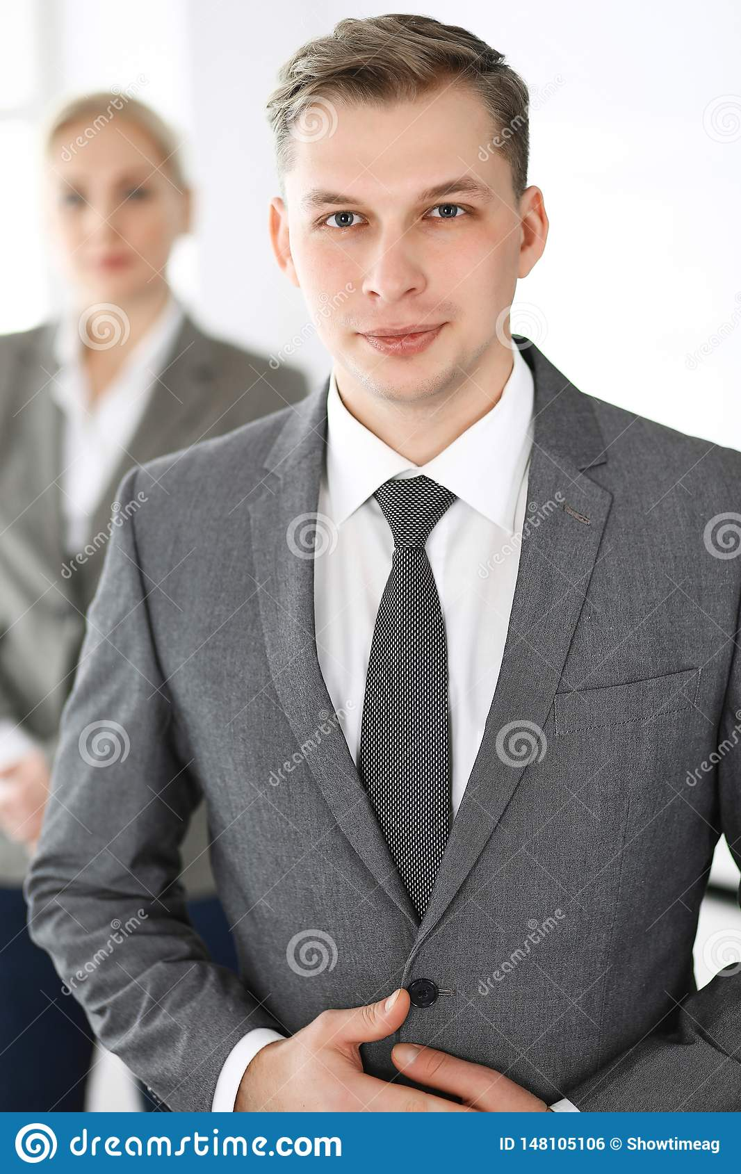 Headshot of businessman standing straight with colleagues at background in office. Group of business people discussing