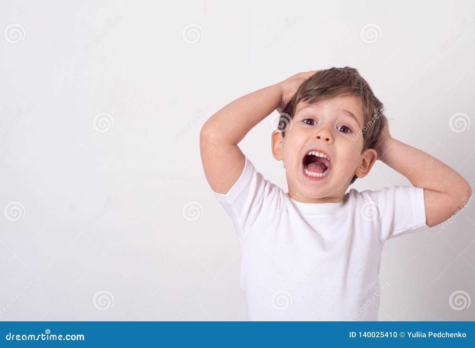 Headshot da boca atrativa impressa da abertura do rapaz pequeno da perplexidade e do choque que guardam as mãos perto da cara