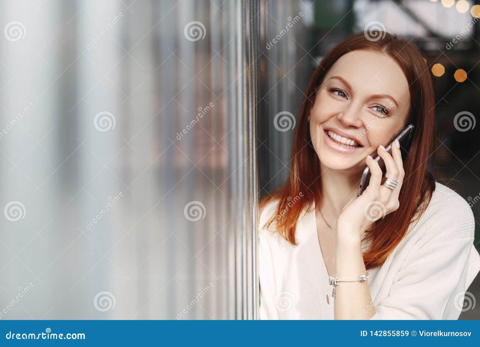 Headshot des lächelnden weiblichen Angestellten mit nettem Gesichtsausdruck, benutzt intelligentes Telefongerät zu Diskussionsinf