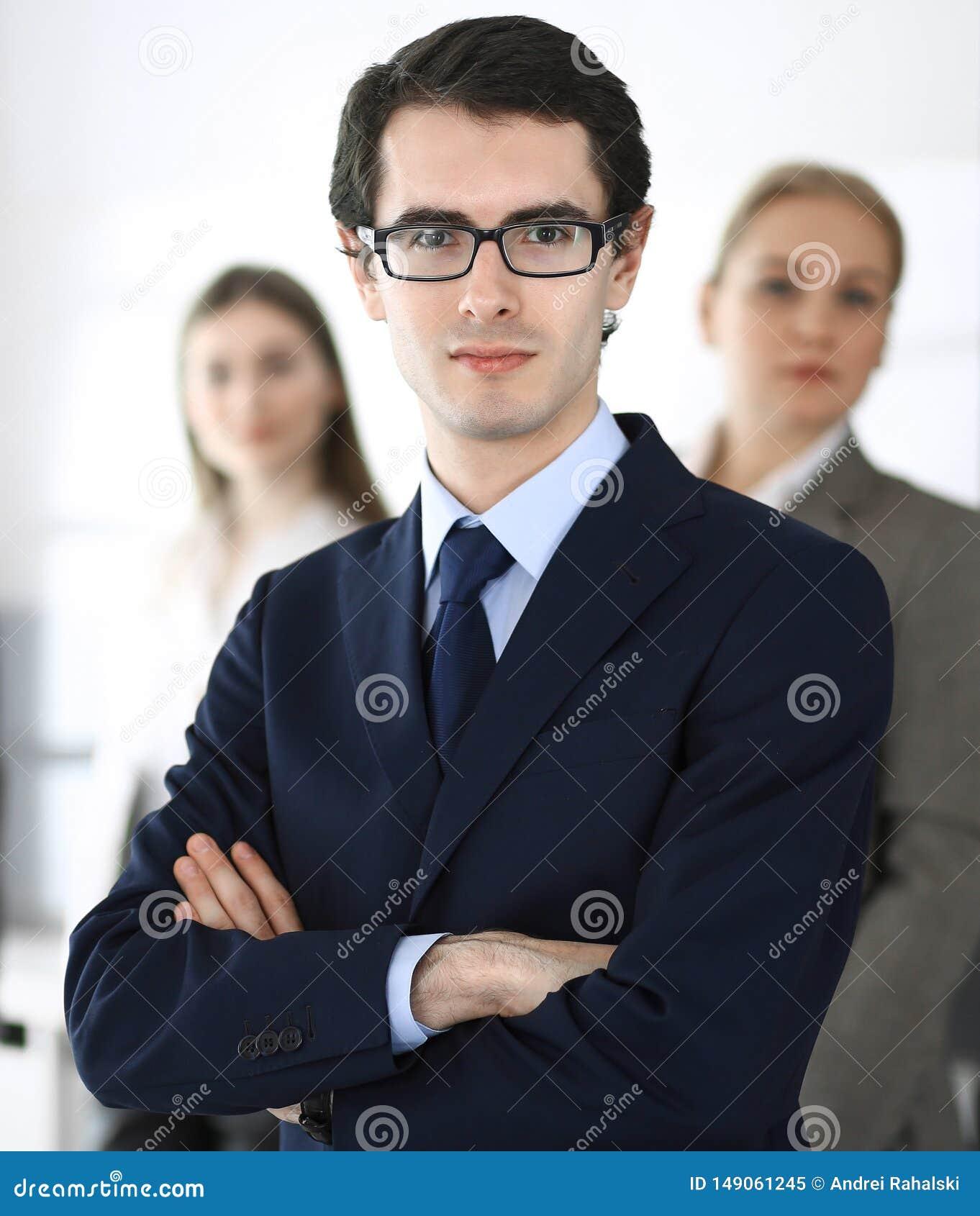 Headshot do homem de neg?cios que est? em linha reta com os colegas no fundo no escrit?rio Grupo de executivos que discutem