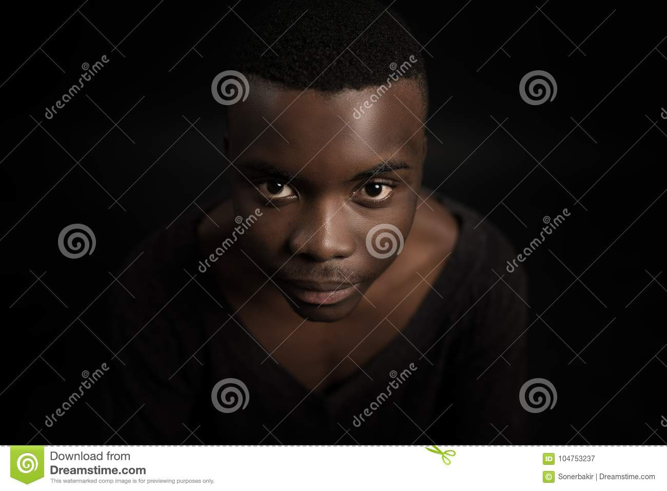 Headshot of serious confident young dark-skinned male standing isolated against black studiobackground.