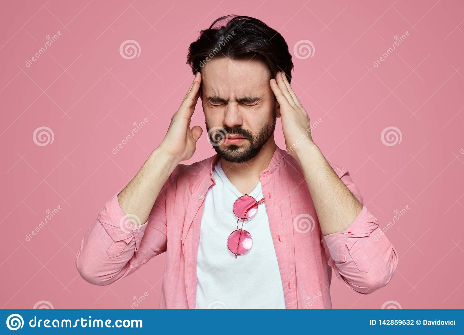 c65fb22e Portrait of a stressed young handsome man dressed in pink shirt having a  headache isolated over pink background. Bearded male student squeezing head  with ...