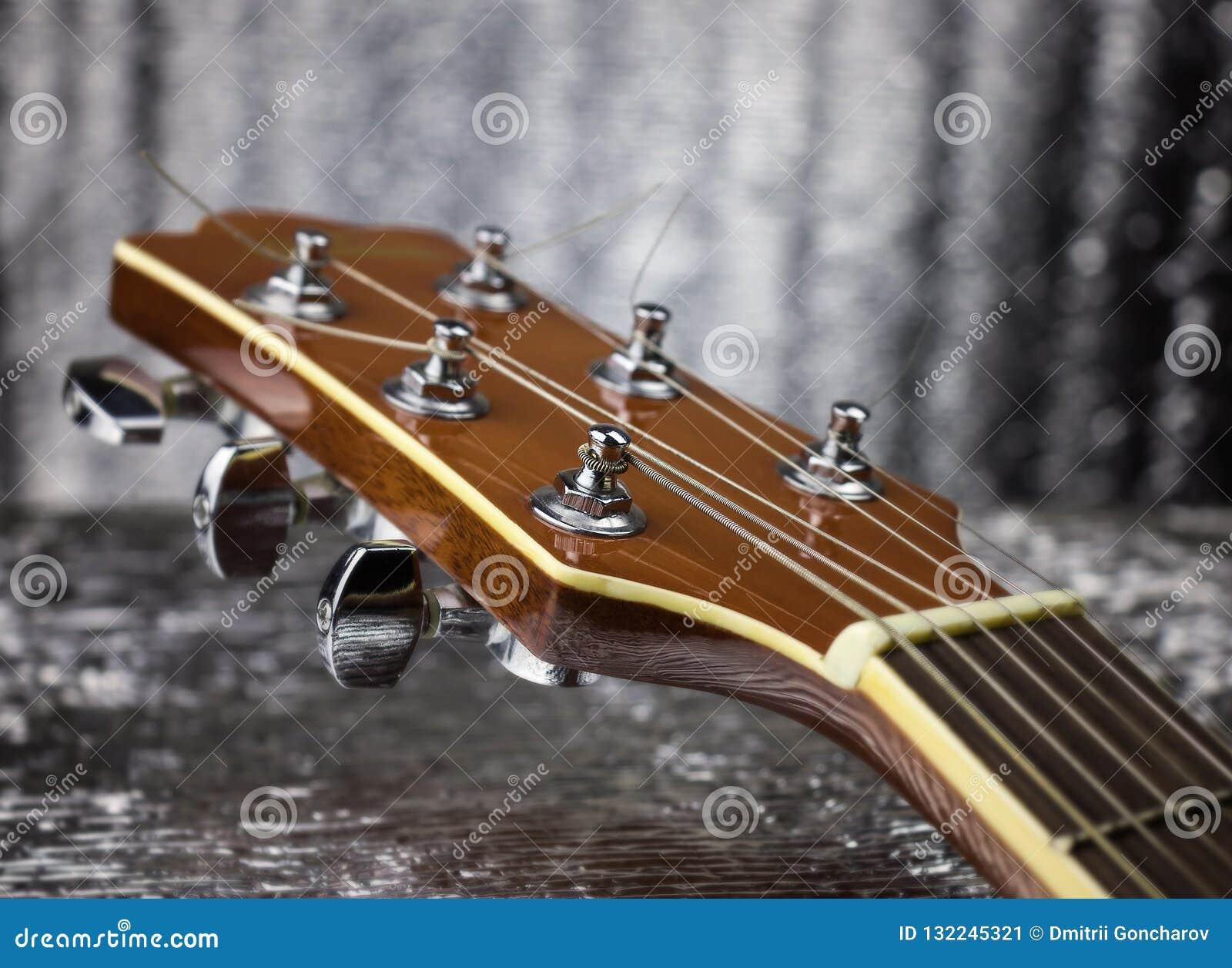 Headstock de uma guitarra clássica sobre o fundo de prata