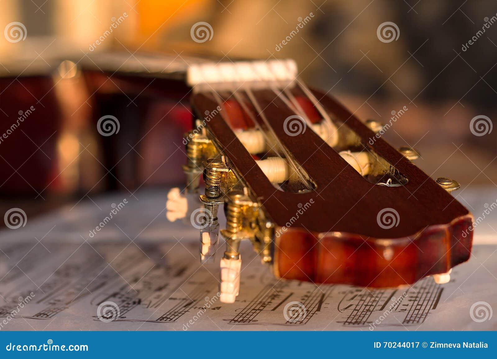 Headstock em notas velhas da música, fim da guitarra acima