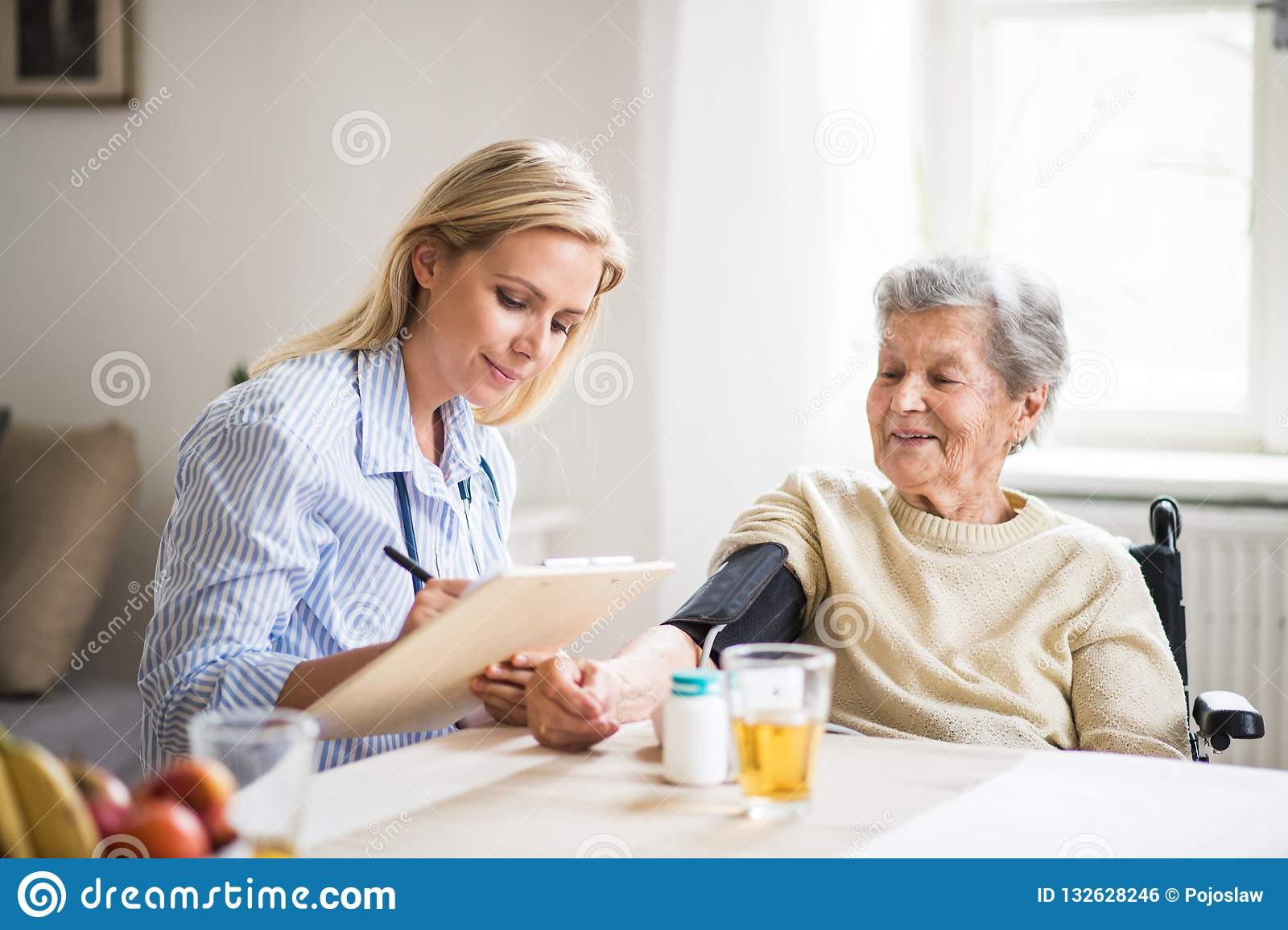 A health visitor measuring a blood pressure of a senior woman at home.