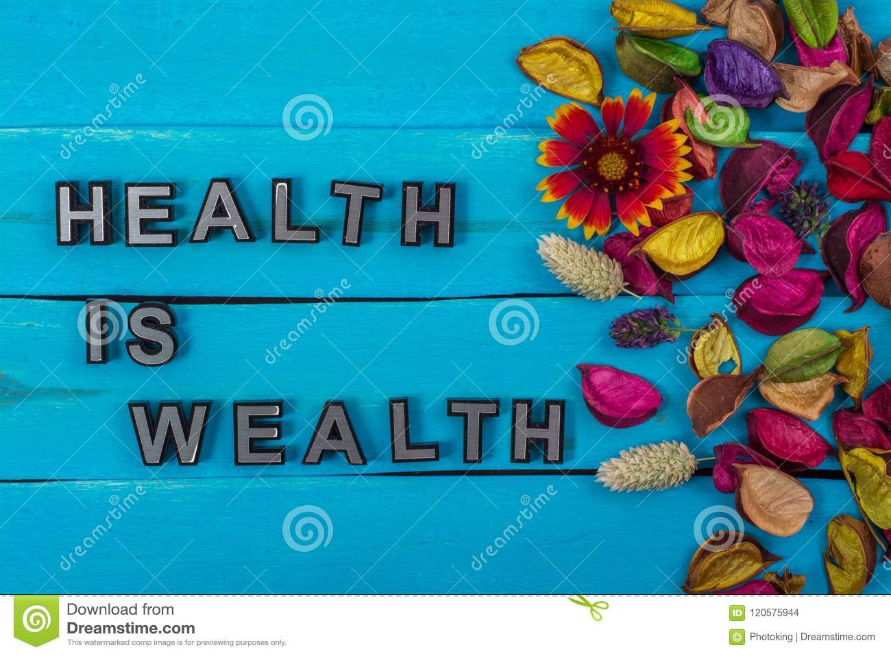 Health is wealth text on blue wood with flower