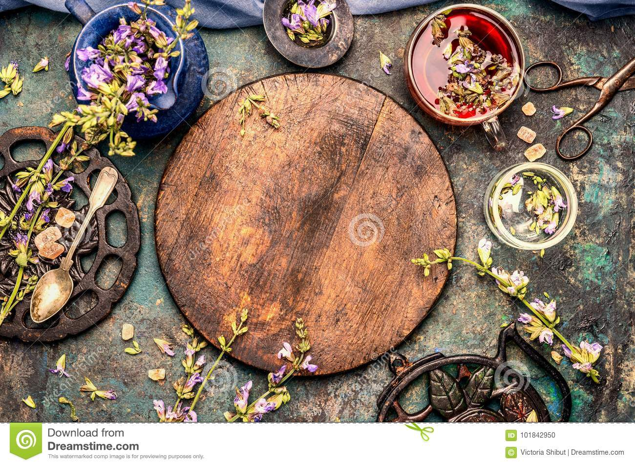Healthful herbs tea setting around round wooden board on rustic background, top view