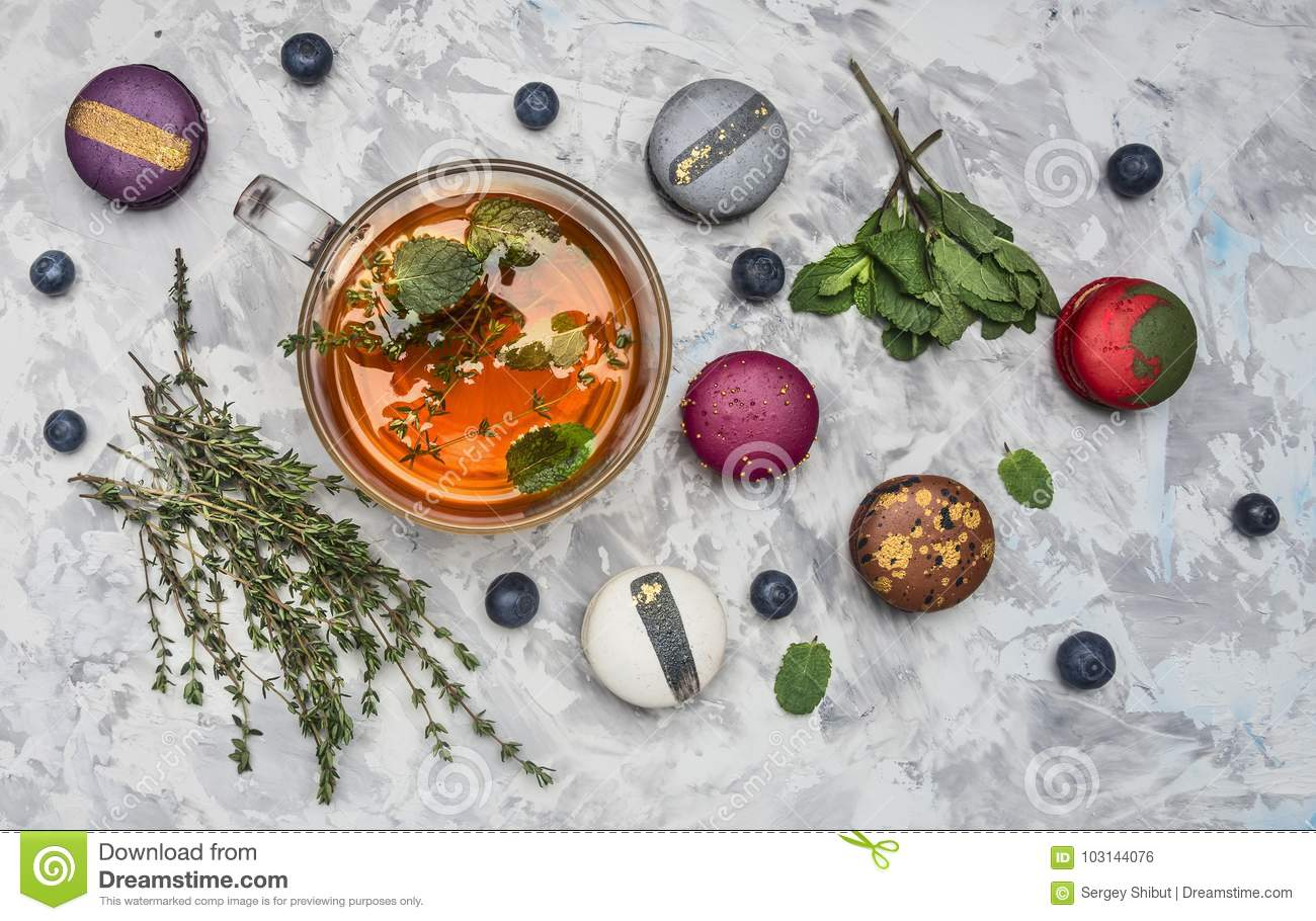 Healthful hot herbal tea with berries, thyme and mint, appetizing, multicolored macaroons on white rustic background, top view
