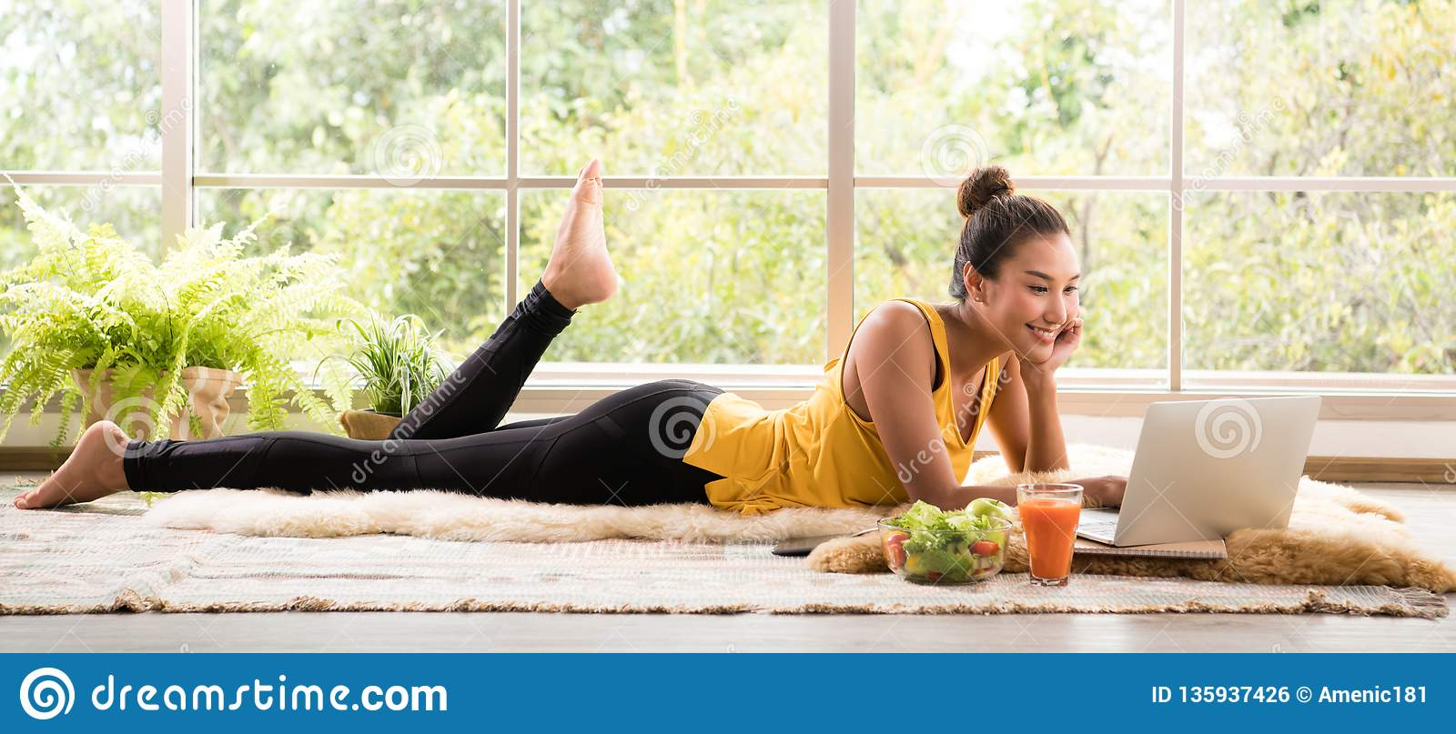 Healthy Asian woman lying on the floor eating salad and looking at laptop computer