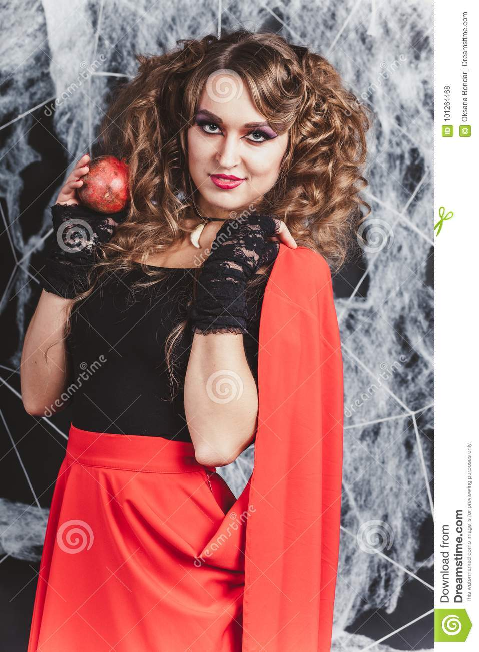 97ade0e937 A healthy beautiful young girl with a pomegranate in her hand. Wears black  blouse and red skirt. Spider web on background. Halloween concept.