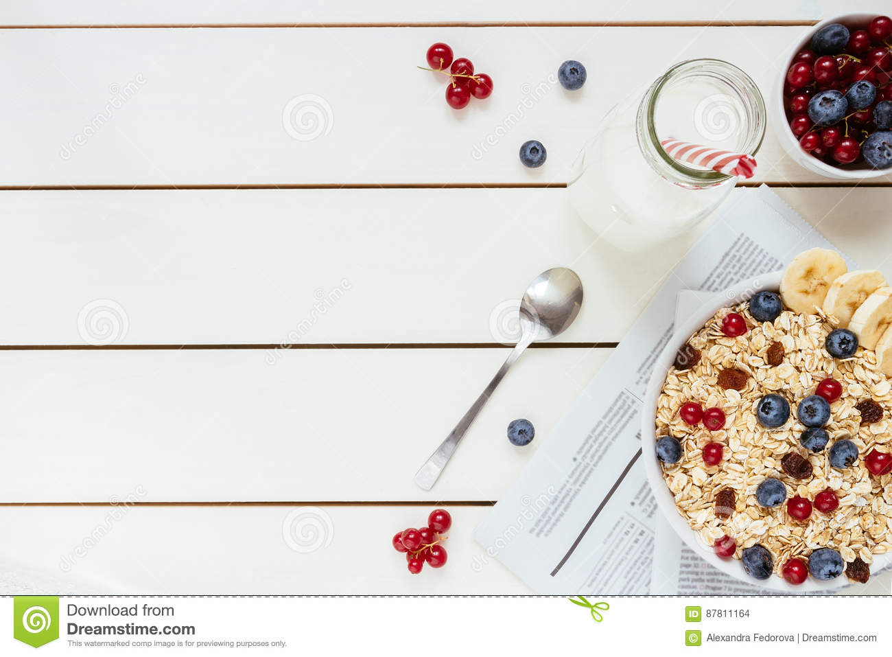 Healthy breakfast with berries and milk on the white wooden table with copy space, top view