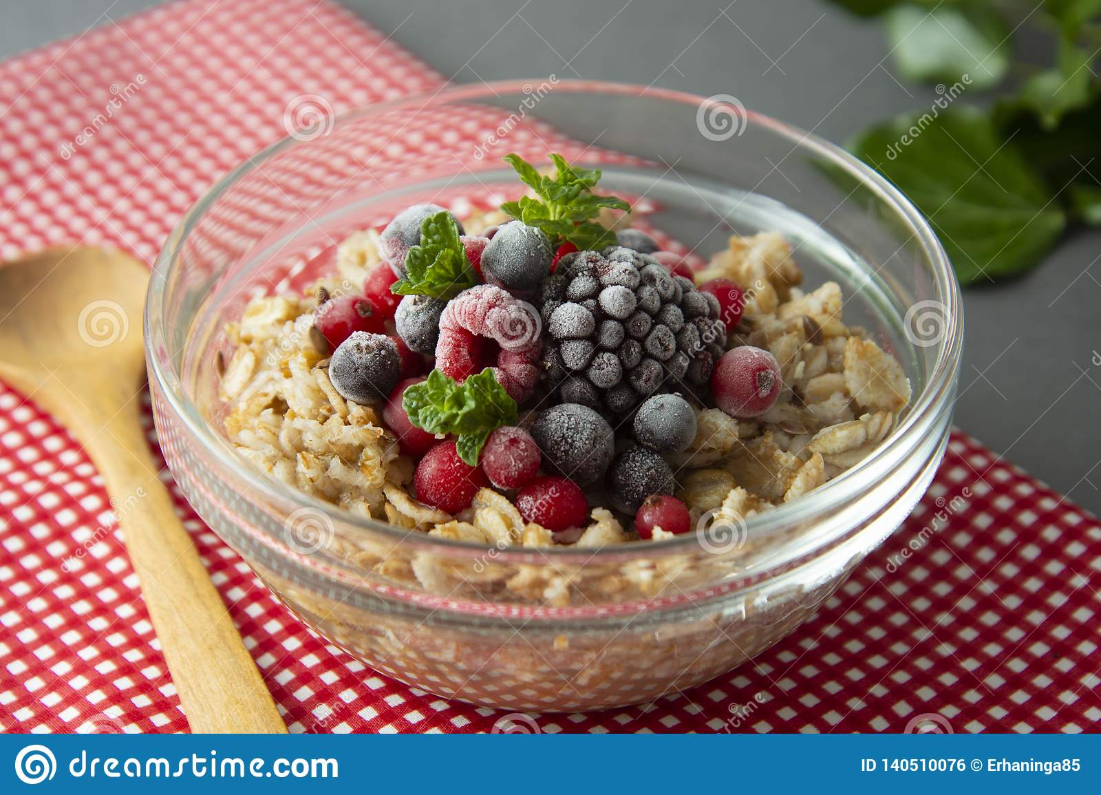 Healthy breakfast in a bowl with oatmeals, frozen berries, fresh strawberries, mint. Oat porridge with fruits
