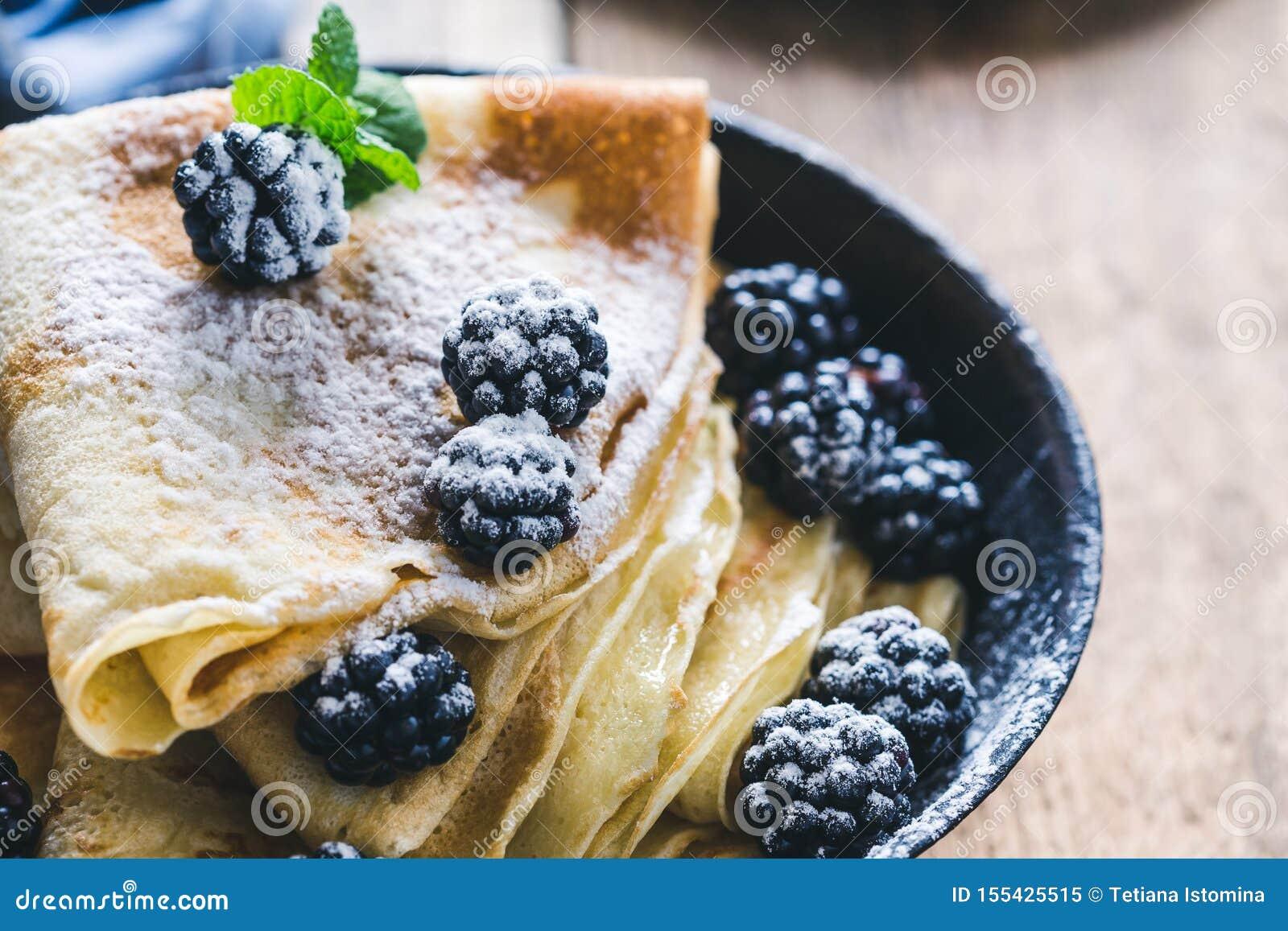 Homemade crepes, fresh summer blackberries powdered sugar