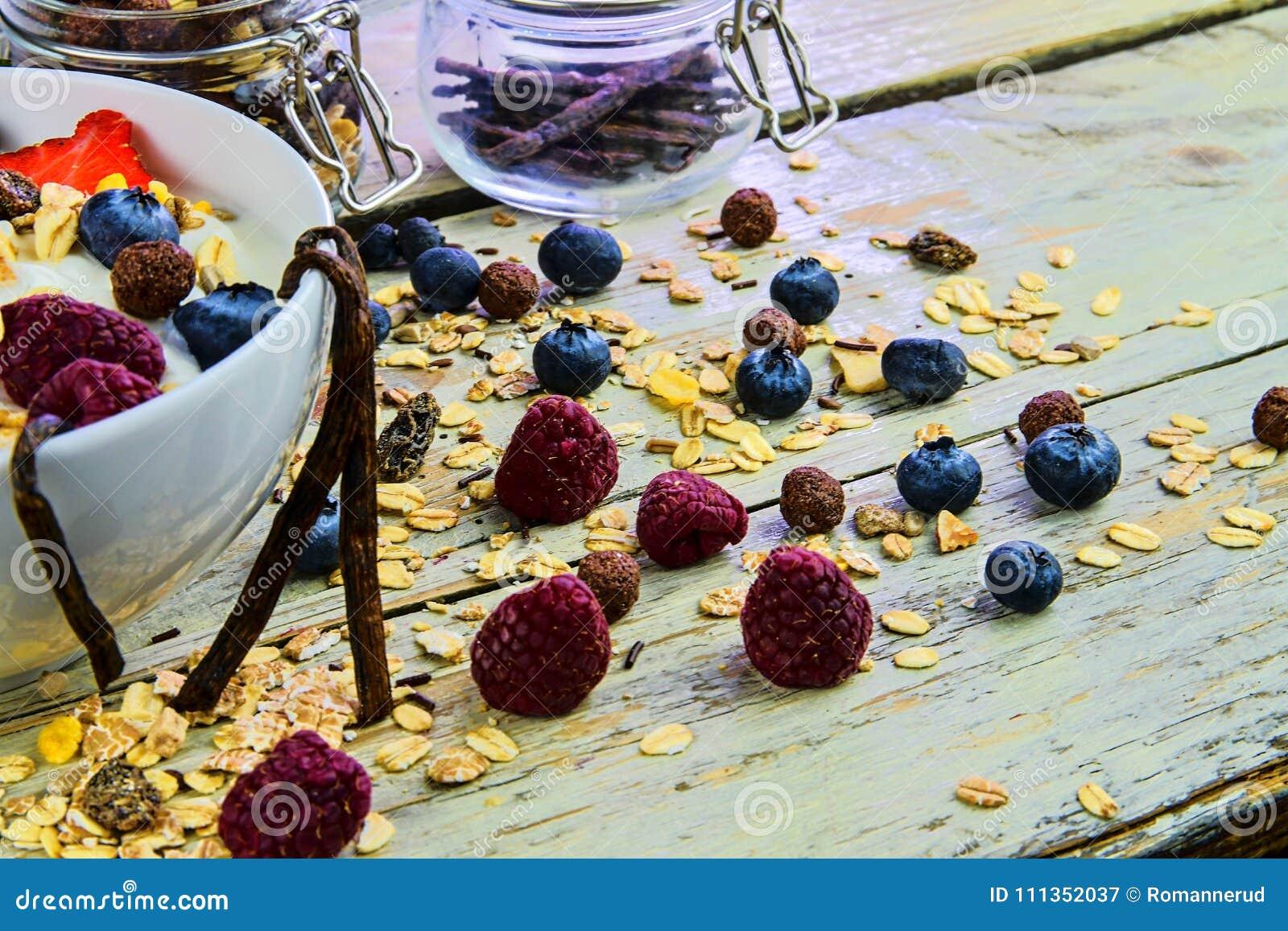 Healthy breakfast, cereal with yoghurt, strawberries, blueberries, raspberries and muesli on wooden rustic background