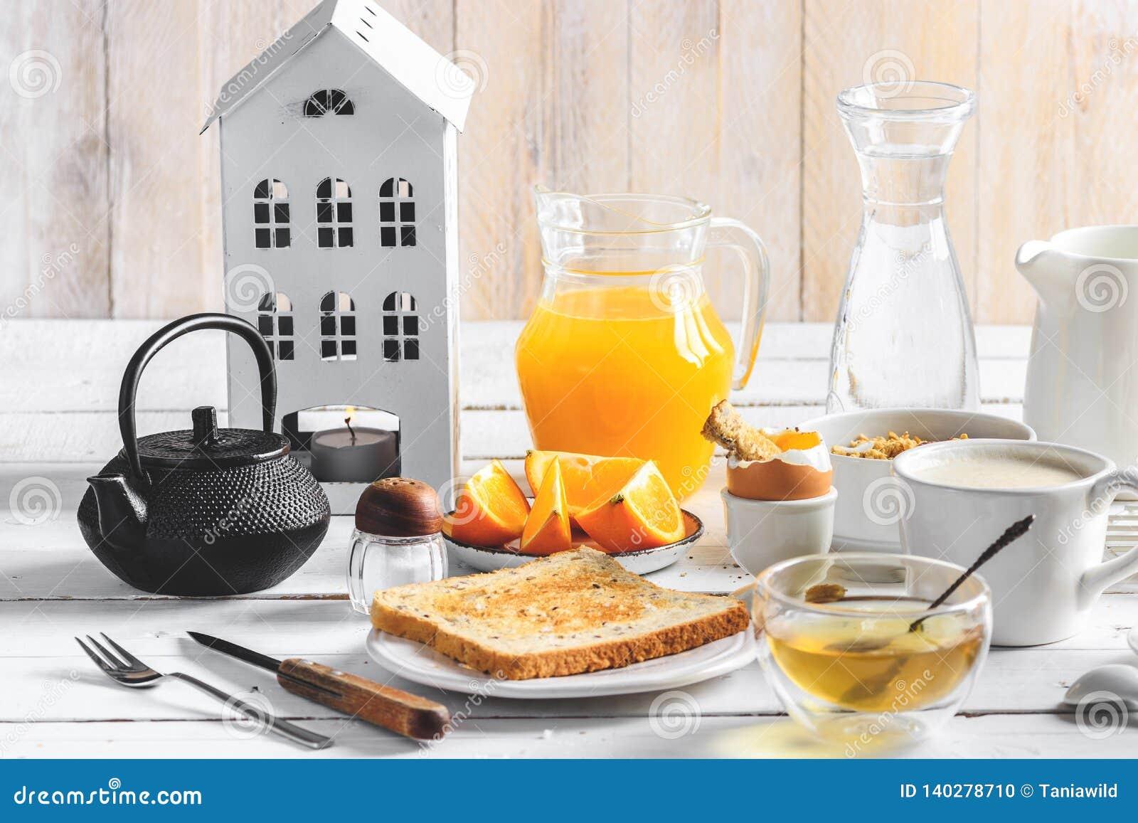 Healthy breakfast eating concept, various morning food - pancakes, soft-boiled egg, toast, oatmeal, granola, fruit, coffee, tea,