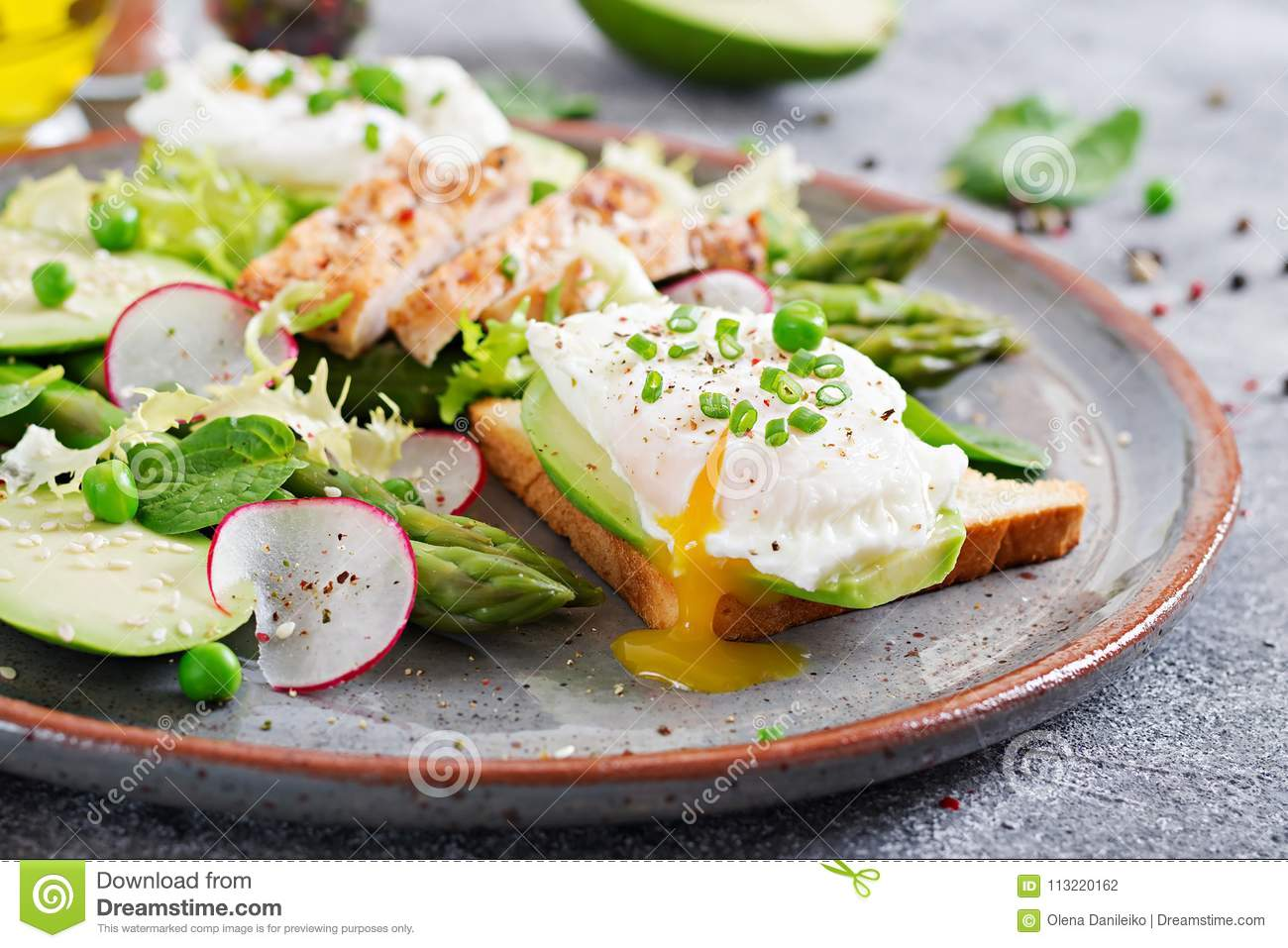 Eggs poached on toast with avocado, asparagus and chicken fillet on grill.
