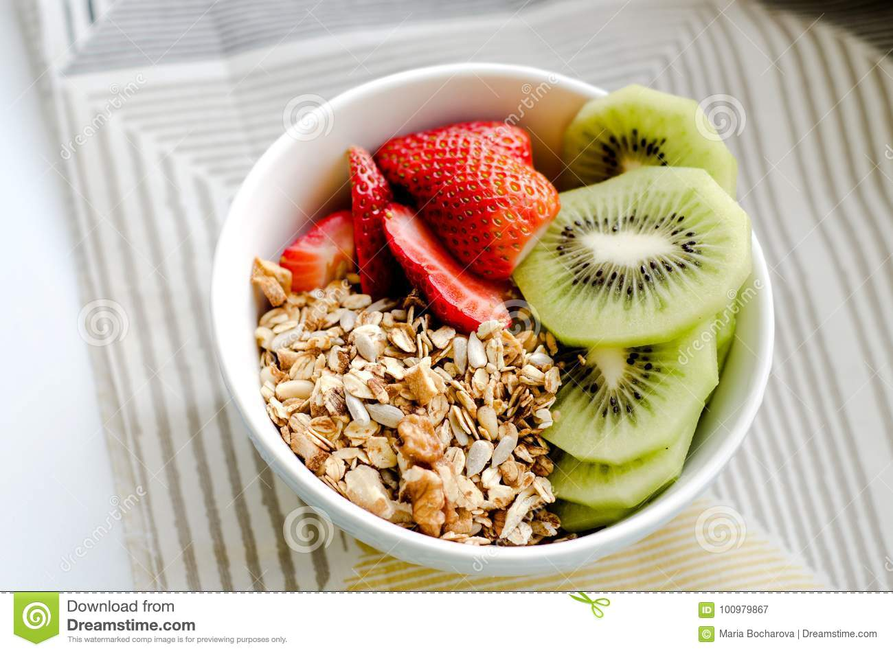 Healthy breakfast fresh granola, muesli in bowl with cereal, nuts, banana fruit, honey with drizzlier, glass of water