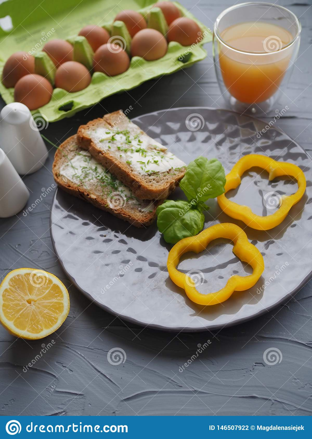 Healthy breakfast with home made bread and eggs and orange juice on grey plate and grey background ideal for culinary blogger or c