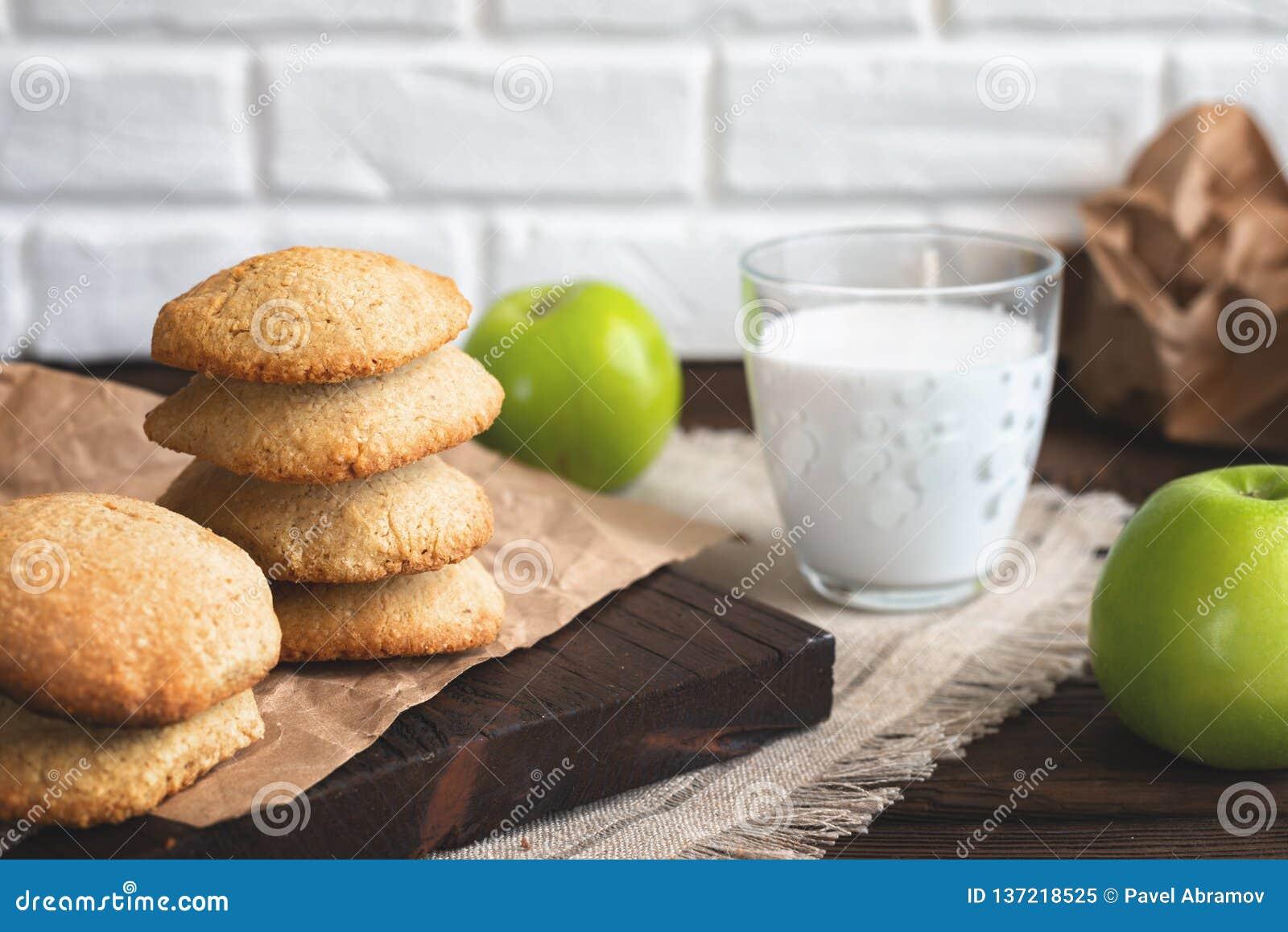 Daily healthy breakfast. Homemade oatmeal cookies, milk, fruit on dark background