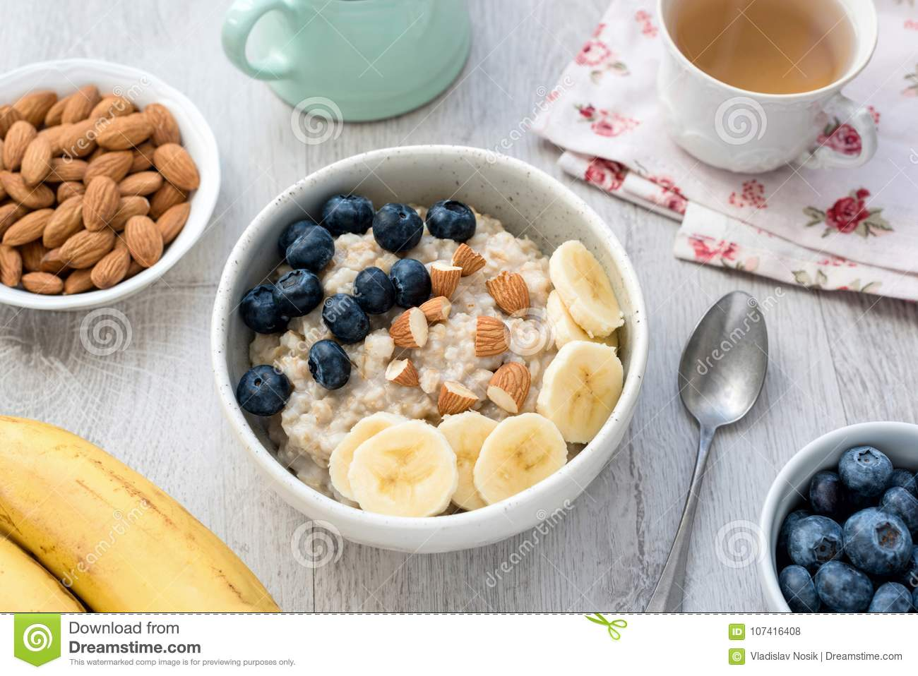 Healthy Breakfast Oatmeal Porridge Bowl with Fruits and Nuts and Cup of Green Tea