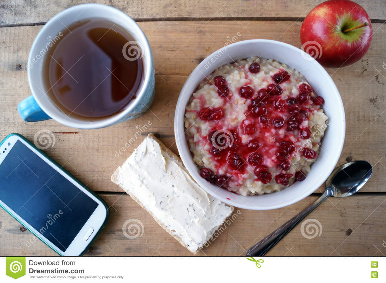 Healthy breakfast, vegetarian. Oatmeal with cranberries, apple, sandwich with cream cheese, tea, mobile phone.