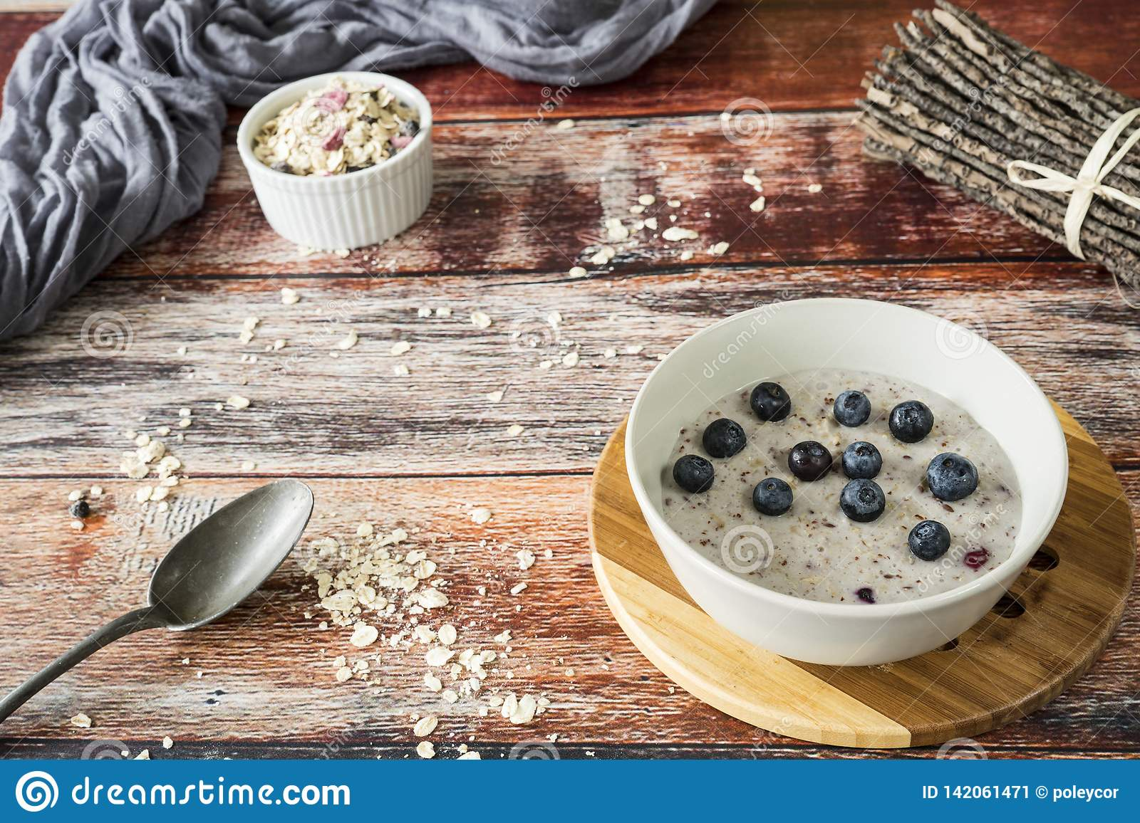 Healthy breakfeast with oats, quinoa, blueberries, on wooden table