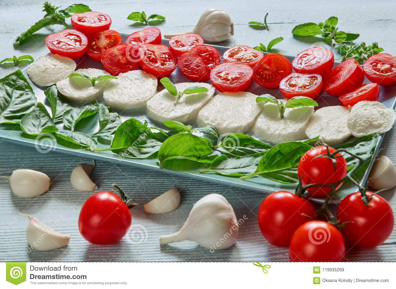 Healthy caprese salad with sliced mozzarella cheese, cherry tomatoes, fresh basil leaves, garlic. Traditional italian food