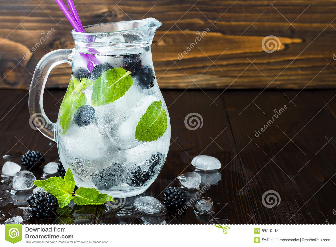 Healthy detox flavored water with blackberry and mint. Cold refreshing berry drink with ice on dark wooden table. Copy space backg