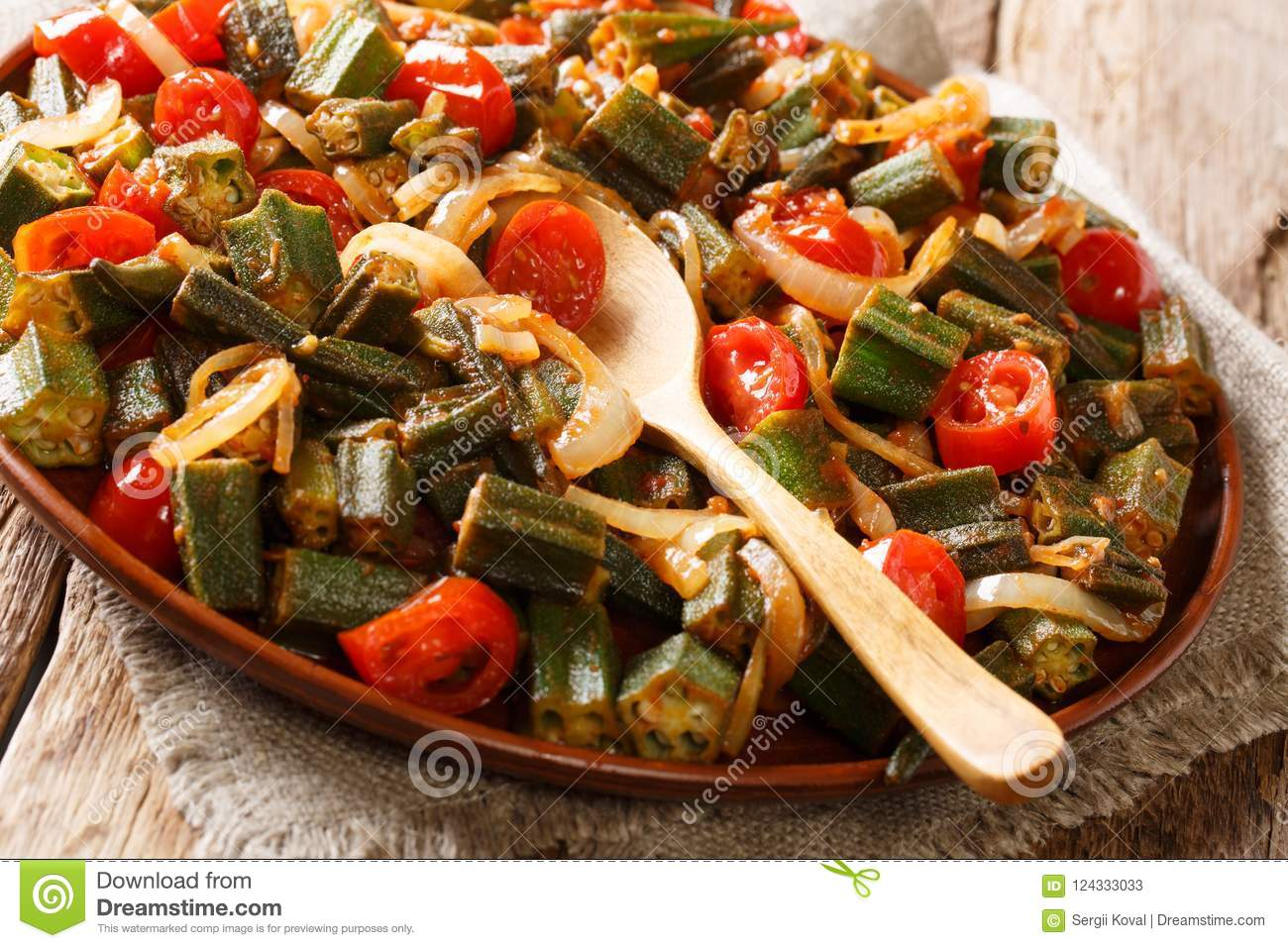 Healthy dietary meal okra with tomatoes and onion close-up on a