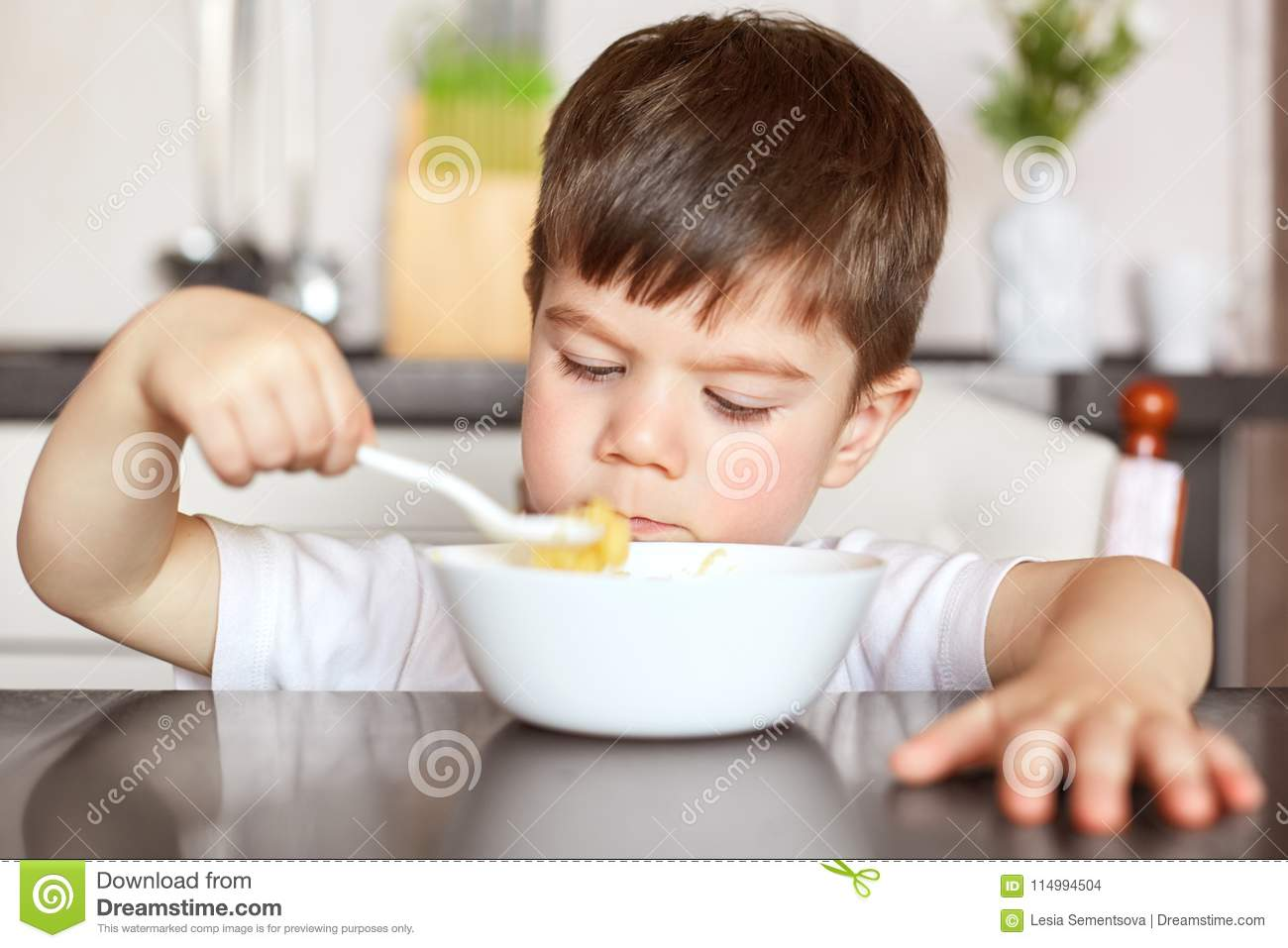 Healthy eating and children concept. Handsome small child eats with great appetite delicious porridge prepared by mother, holds bi