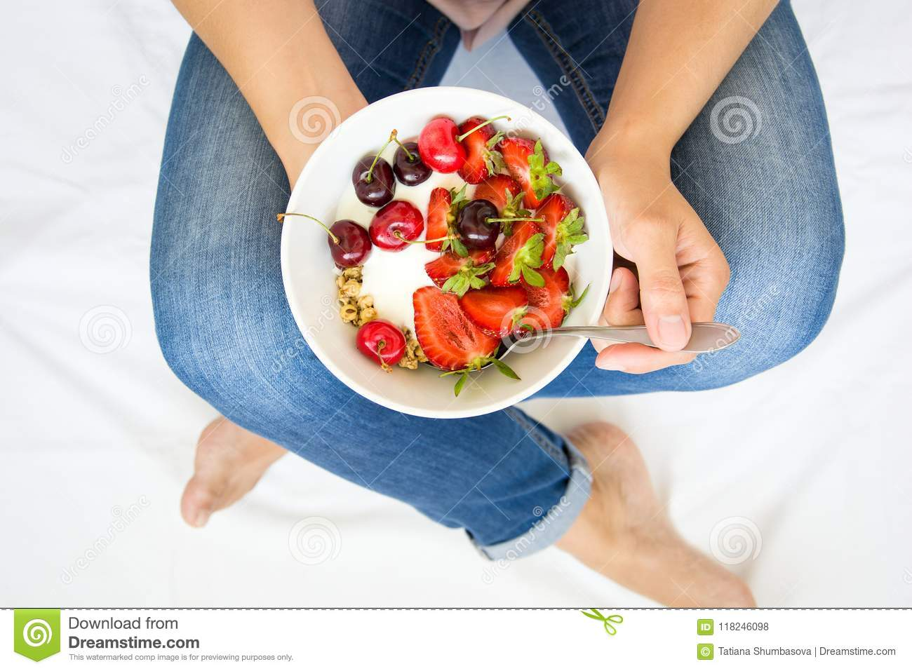 Healthy eating concept. Women`s hands holding bowl with muesli, yogurt, strawberry and cherry. Top view. Lifestyle