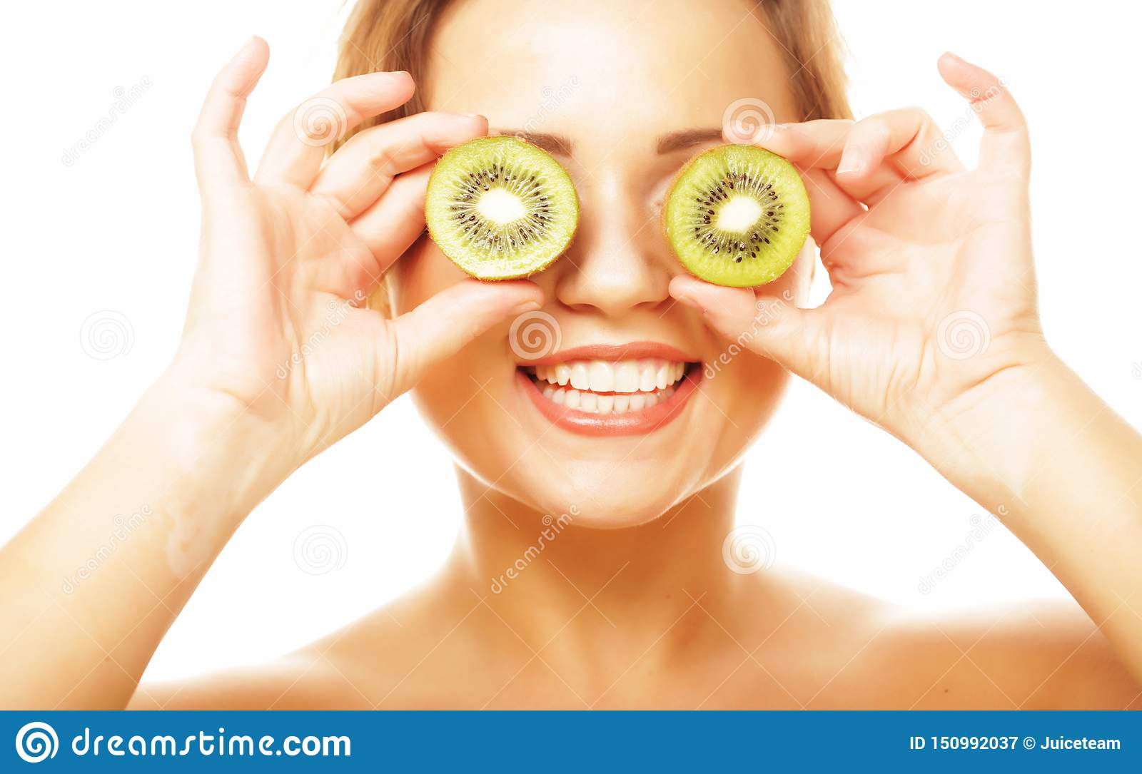 Healthy eating, food and diet concept - funny woman holding kiwi fruit for her eyes.