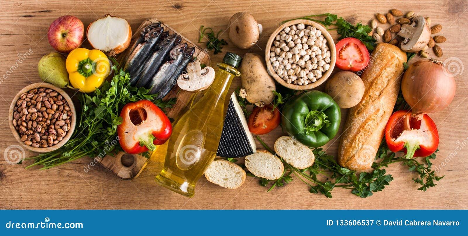 Healthy eating. Mediterranean diet. Fruit,vegetables, grain, nuts olive oil and fish on wood