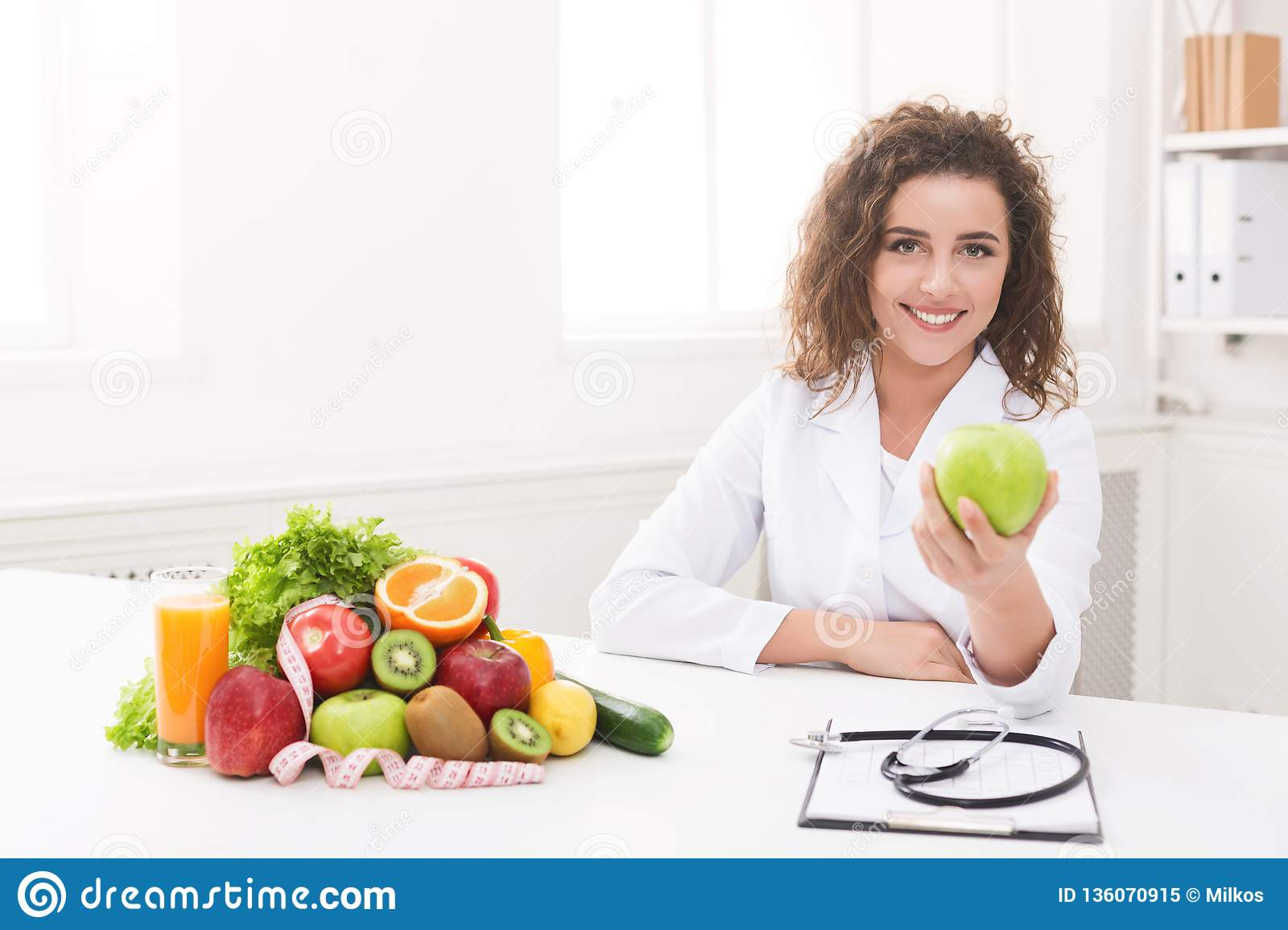 Nutritionist woman offering green apple at camera