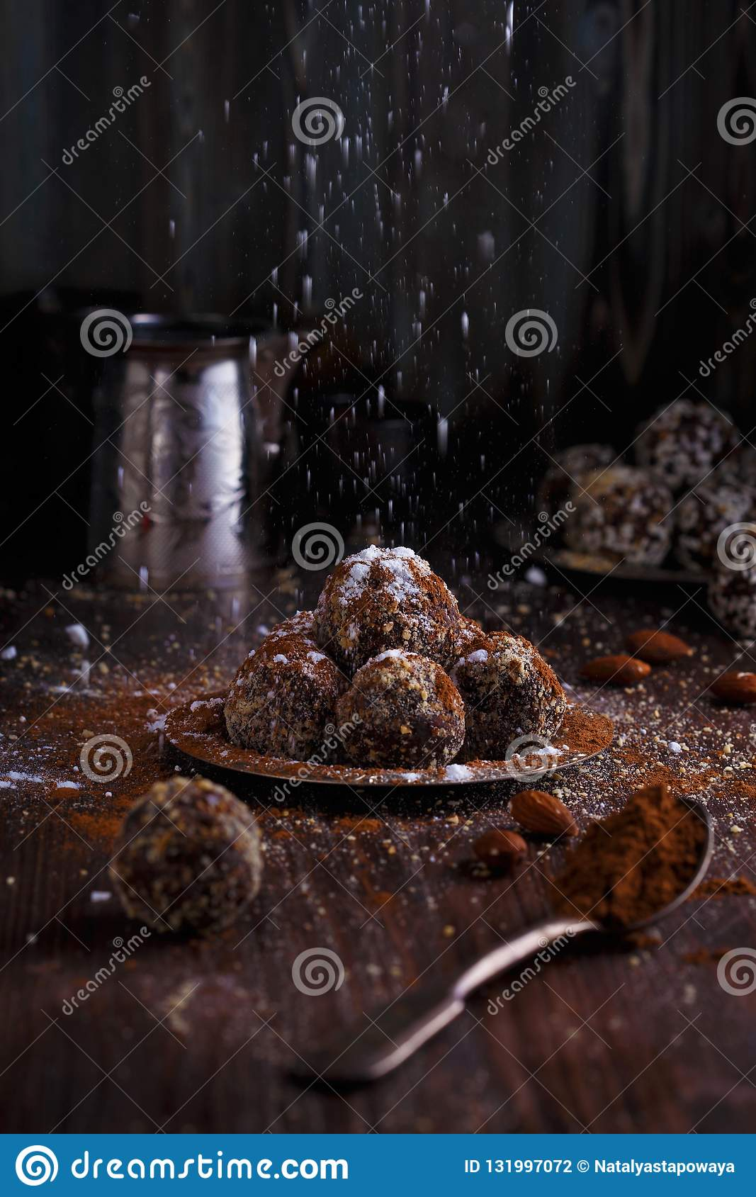 Healthy energy organic vegetarian bites with nuts, dates, honey, cacao and sesame on a dark wooden background