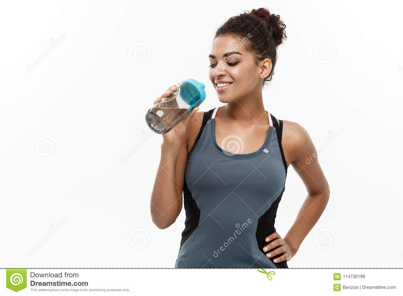 Healthy and Fitness concept - beautiful African American girl in sport clothes drinking water after workout. Isolated on