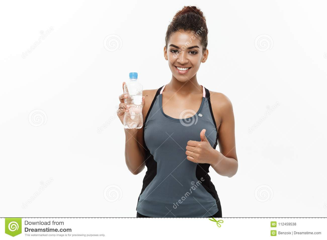 Healthy and Fitness concept - beautiful African American girl in sport clothes holding plastic water bottle after