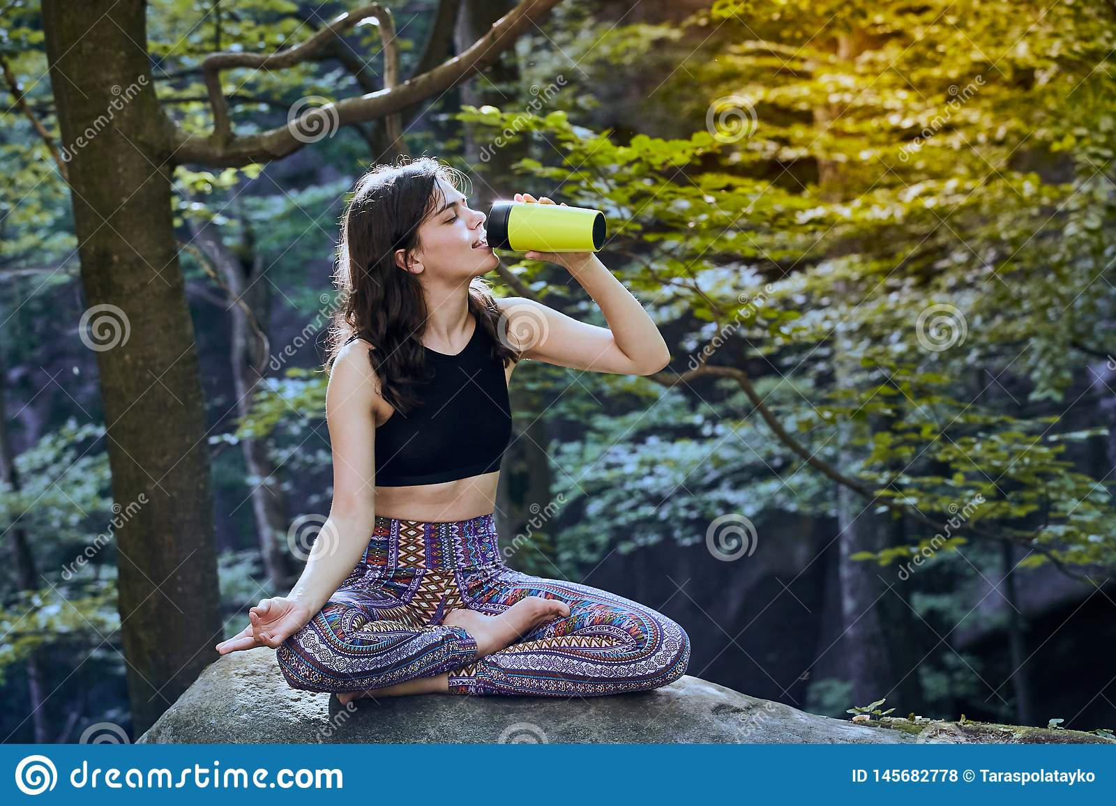 Healthy Fitness Girl Sitting In Lotus Pose And Drinking Water From ...