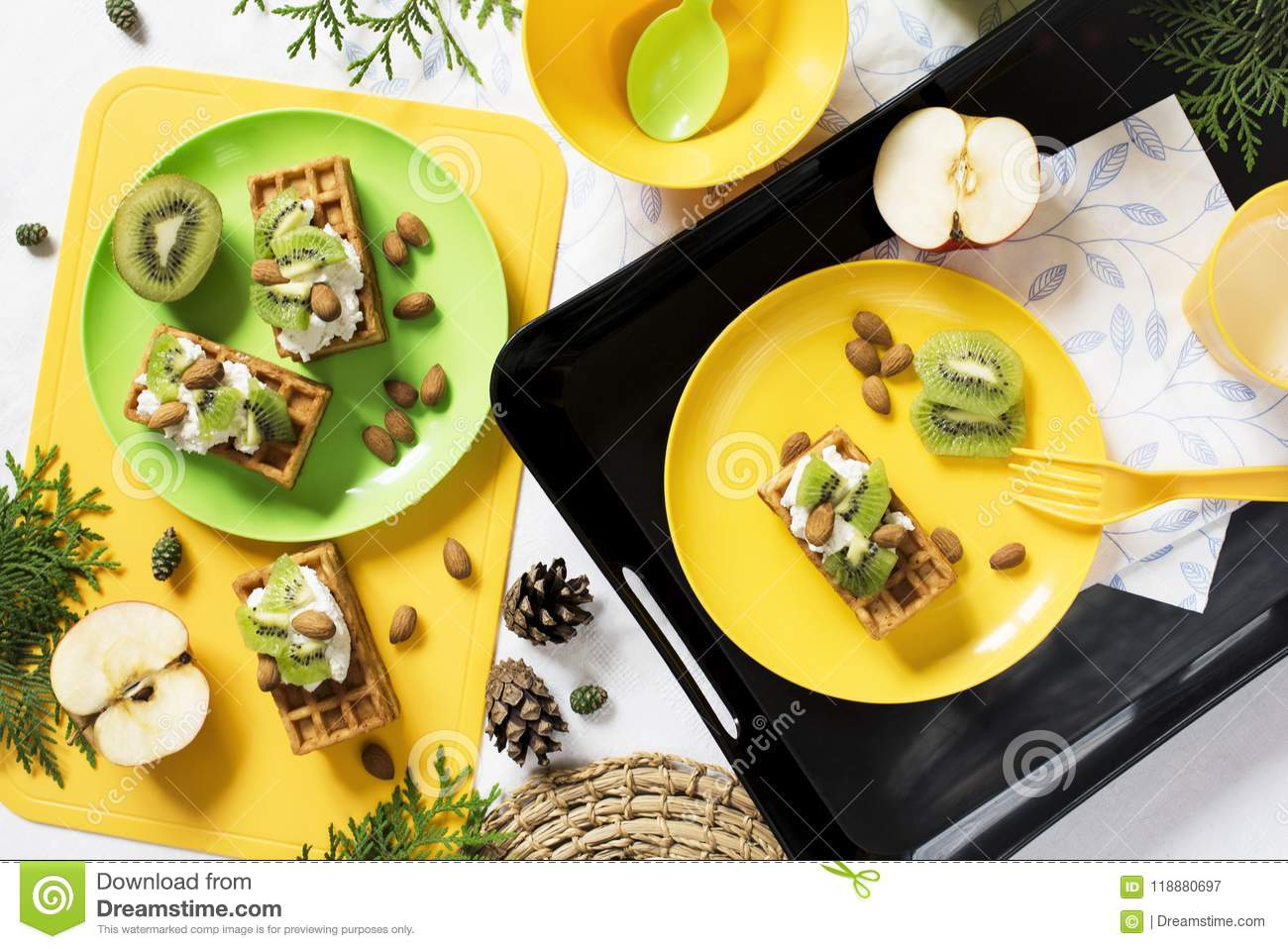 Healthy food. Breakfast with waffles, kiwi, almond, soft cheese, apple, milk on white background.